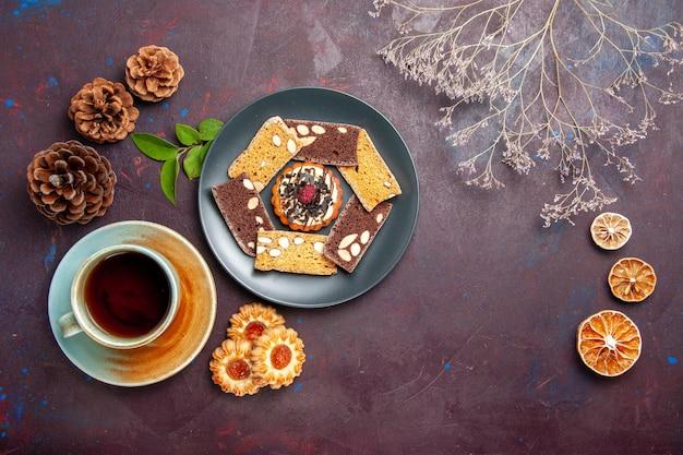 Вид сверху вкусные кусочки торта с небольшим печеньем и чашкой чая на темном столе, печенье, десерт, торт, сладкий