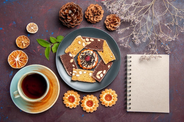 Top view delicious cake slices with little biscuit and cup of tea on the dark background biscuit cookie dessert cake tea sweet