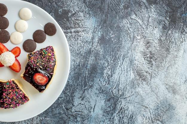 Вид сверху вкусные кусочки торта с маленьким печеньем на темной поверхности
