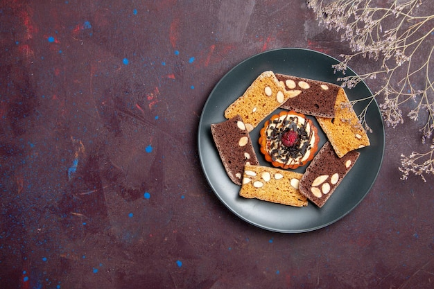 Вид сверху вкусные кусочки торта с орехами и маленьким бисквитом на темном фоне, печенье, десерт, торт, сладкий чай