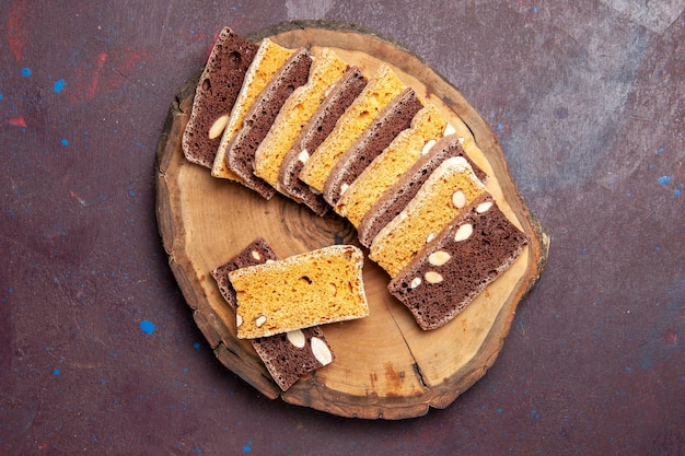 Top view delicious cake slices with nuts on dark background tea cake sugar cookie pie biscuit sweet