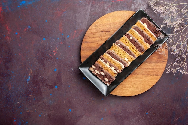 Top view delicious cake slices with nuts inside cake pan on dark background sweet tea cake sugar cookies pie biscuit