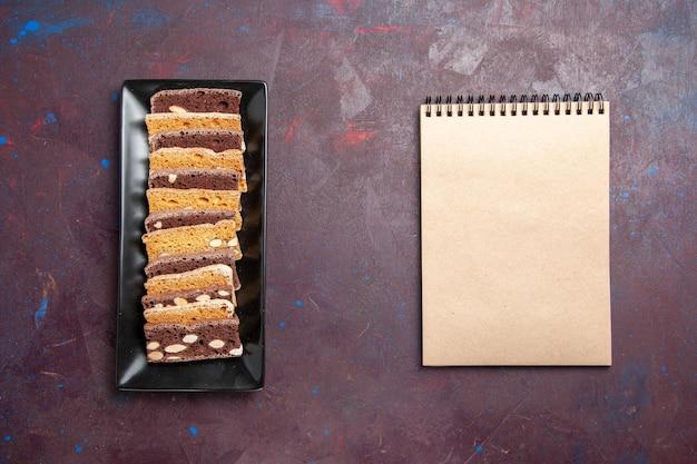 어두운 배경 달콤한 차 케이크 설탕 쿠키 파이 비스킷에 케이크 팬 안에 견과류와 함께 상위 뷰 맛있는 케이크 조각