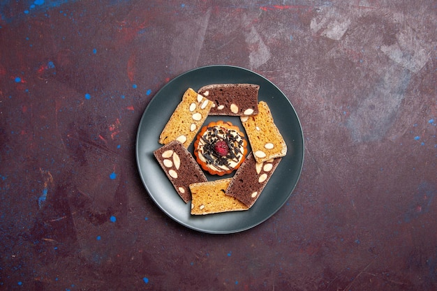 Top view delicious cake slices with nuts and little biscuit on dark background biscuit cookie sweet dessert cake