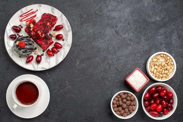 Vista dall'alto deliziose fette di torta con tè alle noci e cornioli su uno spazio grigio