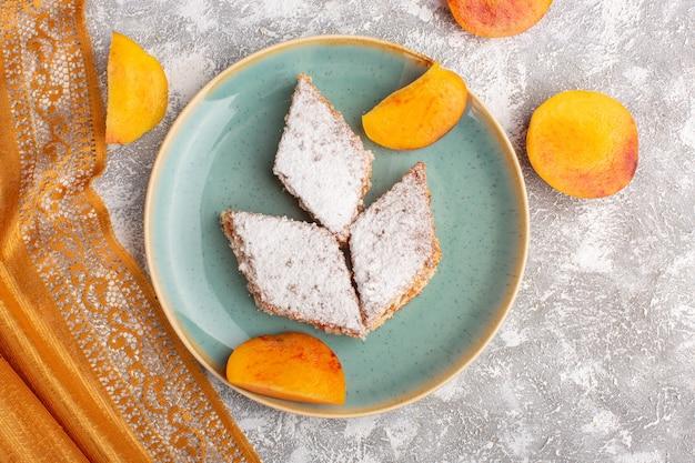 Вид сверху вкусные кусочки торта с сахарной пудрой и нарезанными персиками внутри тарелки на столе, выпечка из сладкого бисквитного торта