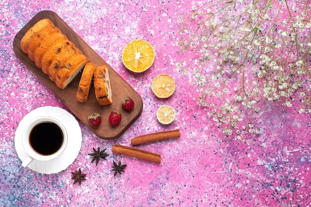 Вид сверху вкусный сладкий и вкусный торт, нарезанный чашкой чая с корицей на розовом столе.