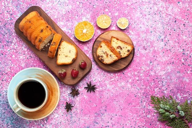 ピンクの机の上でお茶とスライスした甘くておいしいケーキの上面図。