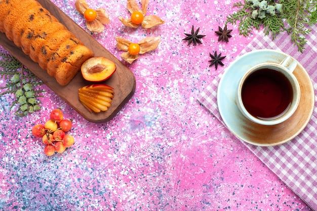 Vista dall'alto deliziosa torta dolce e gustosa con prugne e ciliegie sulla scrivania rosa.