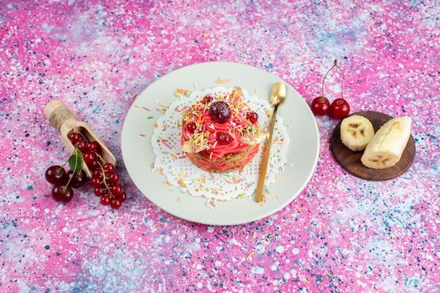 色付きの背景にキャンディーバナナとチェリーのおいしいケーキを平面図ビスケット砂糖甘い生地を焼く