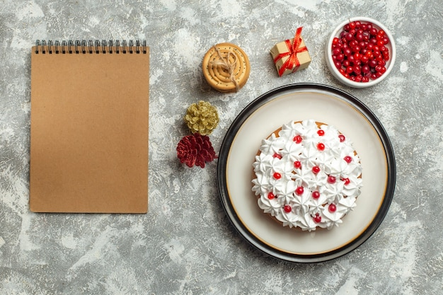 Top view of delicious cake with cream currant on a plate and gift boxes stacked cookies conifer cones next to notebook on gray background