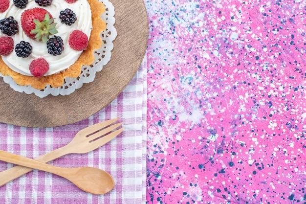 Vista dall'alto di una deliziosa torta con panna e frutti di bosco freschi su luce, biscotto torta ai frutti di bosco