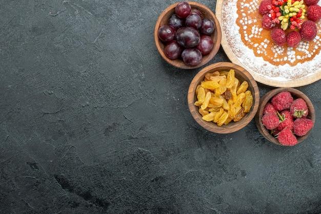 灰色の背景にラズベリーとフルーツのトップビューおいしいケーキ甘いケーキパイフルーツベリークッキー