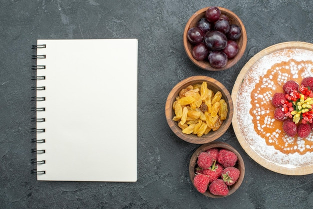 Top view delicious cake with raspberries and fruits on a grey background sweet cake pie fruit berry cookie