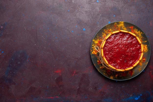 Vista dall'alto deliziosa torta con crema rossa e biscotti sui biscotti dolci della torta di zucchero della torta del biscotto scuro della scrivania