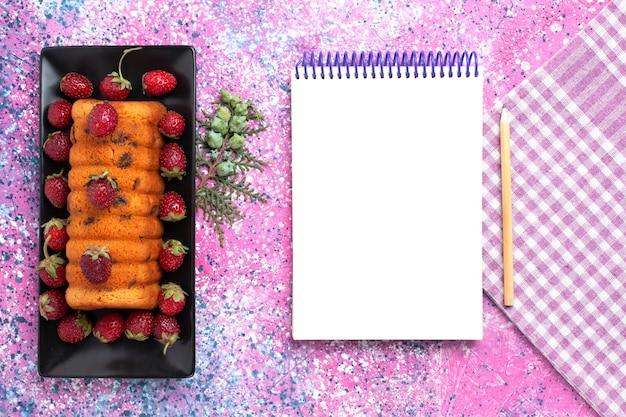 ピンクの机の上に赤い新鮮なイチゴとトップビューのおいしいケーキ。