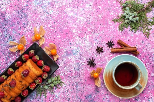 Вид сверху вкусный торт с красной клубникой и чашкой чая на розовом столе.