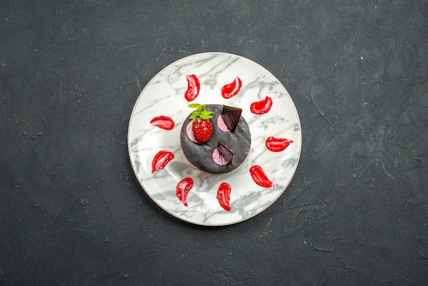 暗い背景の楕円形のプレートにイチゴとチョコレートのトップビューおいしいケーキ