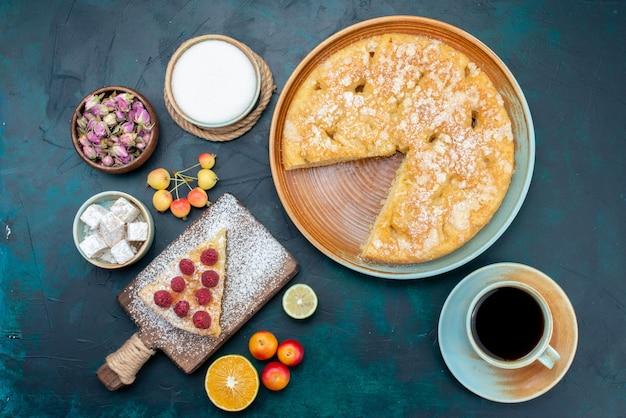 ダークブルーのデスクパイケーキ甘いビスケットシュガーにお茶と果物のトップビューおいしいケーキ