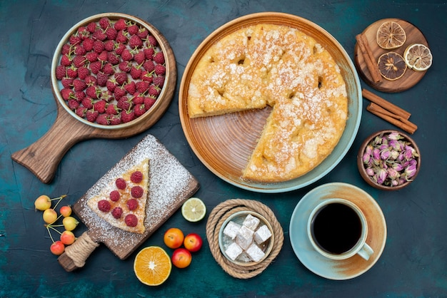 Vista dall'alto una deliziosa torta con tè e frutta sullo zucchero blu scuro della torta della torta della scrivania