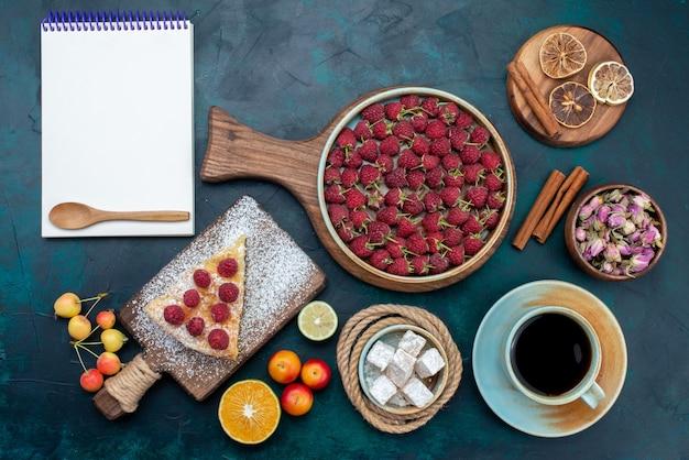 Vista dall'alto una deliziosa torta con tè lamponi e frutta sullo zucchero blu scuro della torta della torta della scrivania