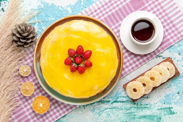 Вид сверху вкусный торт с желтым сиропом и свежей красной клубникой на голубом столе, бисквитный торт, выпечка сладкий сахарный пирог, чай