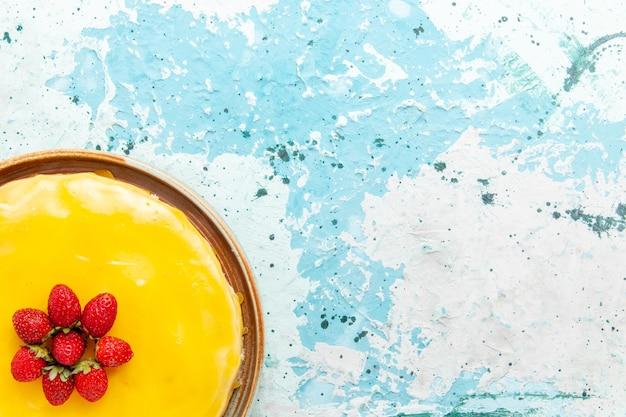 青い机の上に黄色いシロップと赤いイチゴのトップビューおいしいケーキビスケットケーキ甘いパイシュガーティー