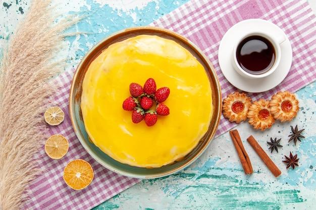Вид сверху вкусный торт с желтым сиропом свежая красная клубника и чашка чая на синей поверхности бисквитный торт испечь сладкий сахарный пирог чай