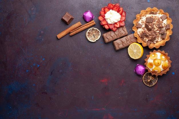 Vista dall'alto di deliziose torte insieme a cannella e caramelle sulla superficie scura
