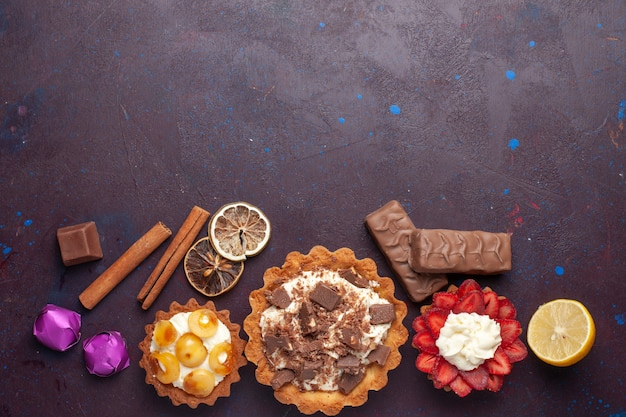 Top view of delicious cakes along with cinnamon and candies on the dark surface
