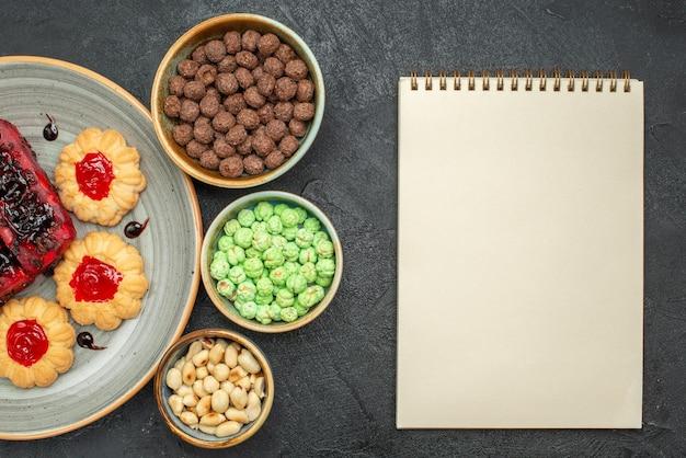 Вид сверху вкусные торты фруктовые сладости с печеньем и конфетами на темном фоне сахарное печенье бисквитный торт сладкий пирог чай