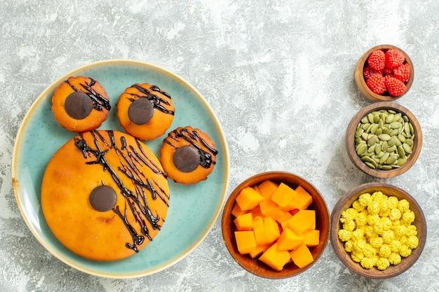 Vista dall'alto deliziose torte con glassa al cioccolato e caramelle sulla superficie bianca caramella tè dolce biscotto biscotto torta