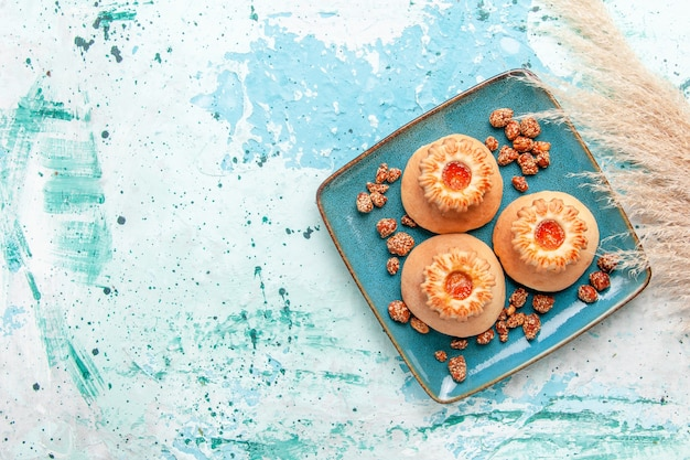 밝은 파란색 배경에 쿠키와 달콤한 견과류와 함께 상위 뷰 맛있는 케이크는 비스킷 케이크 달콤한 설탕 너트를 구워