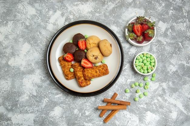 Vista dall'alto deliziose torte con biscotti, caramelle e fragole su sfondo bianco biscotto zucchero torta torta dolce tè biscotto