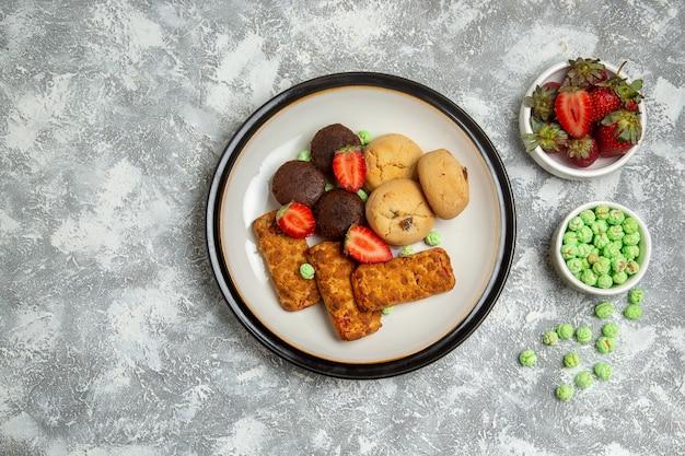 Vista dall'alto deliziose torte con biscotti, caramelle e fragole su sfondo bianco biscotto zucchero torta dolce tè biscotto