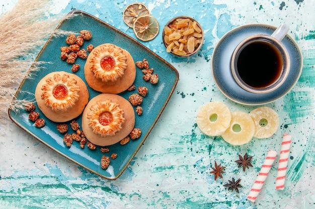 밝은 파란색 표면에 쿠키 커피와 달콤한 견과류와 함께 상위 뷰 맛있는 케이크는 비스킷 케이크 달콤한 설탕을 구워