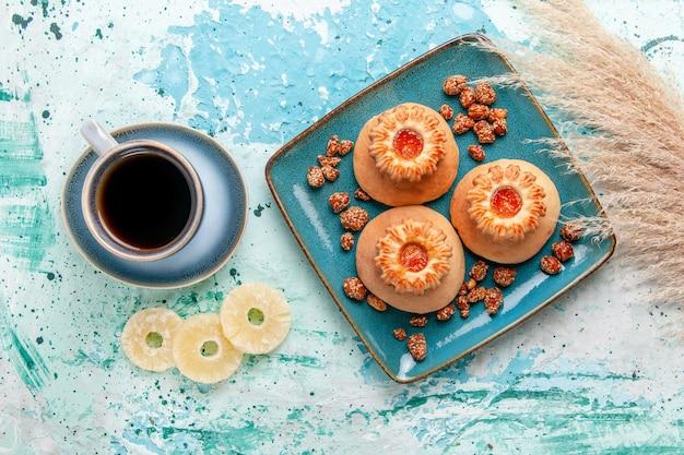 Vista dall'alto deliziose torte con biscotti caffè e noci dolci sulla superficie azzurra cuocere torta biscotto zucchero dolce dado
