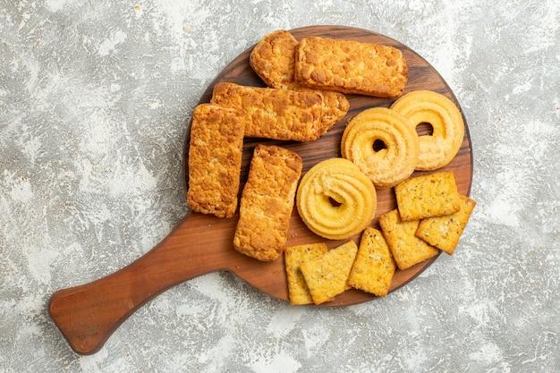 Vista dall'alto deliziose torte con cracker e biscotti su sfondo bianco