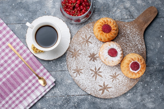 Top view delicious cakes with cup of coffee and fresh red cranberries on the grey rustic desk biscuit sweet fruit