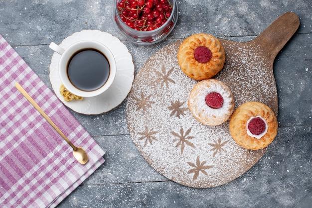 Вид сверху вкусные торты с чашкой кофе и свежей красной клюквой на сером деревенском столе, печенье, сладкие фрукты