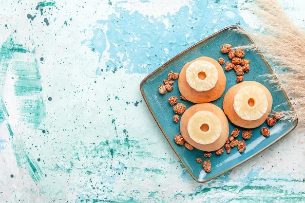Vista dall'alto deliziose torte con anelli di ananas essiccato e noci dolci su sfondo azzurro cuocere una torta di biscotti con zucchero dolce dado