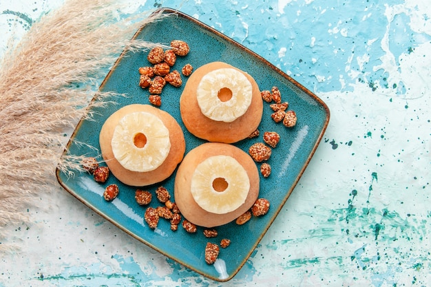 Top view delicious cakes with dried pineapple rings and sweet nuts on light blue background bake biscuit cake sweet sugar nut