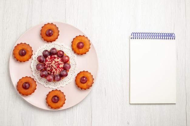 白いテーブルの上のプレート、パイのデザートケーキの中にブドウが入ったトップビューのおいしいケーキ