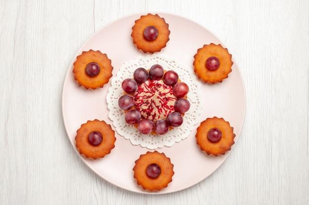 Vista dall'alto deliziose torte con l'uva all'interno del piatto sulla torta da dessert di frutta da tavola bianca