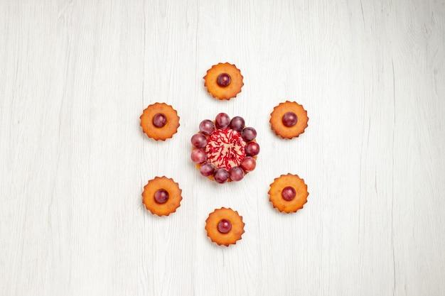 Вид сверху вкусные пирожные с виноградом на белом столе, десертное печенье, бисквитное печенье