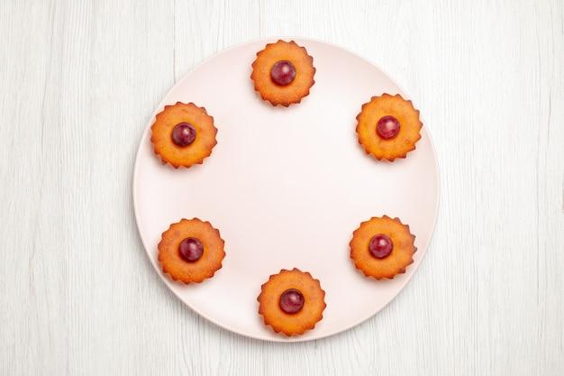 白いテーブルの上のブドウとおいしいケーキの上面図ビスケットデザートパイ