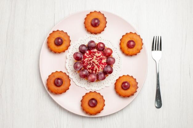 白いテーブルの上のブドウとおいしいケーキの上面図ビスケットパイデザート