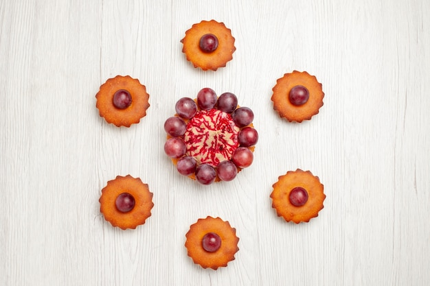 白いテーブルの上のブドウとおいしいケーキの上面図デザートビスケットパイクッキー