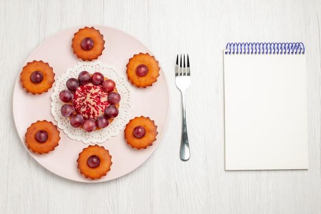 Vista dall'alto deliziose torte con l'uva sulla torta di dessert biscotto tavolo bianco