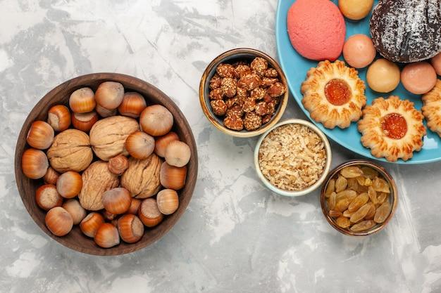 Vista dall'alto deliziose torte con noci macarons e biscotti sulla superficie bianca
